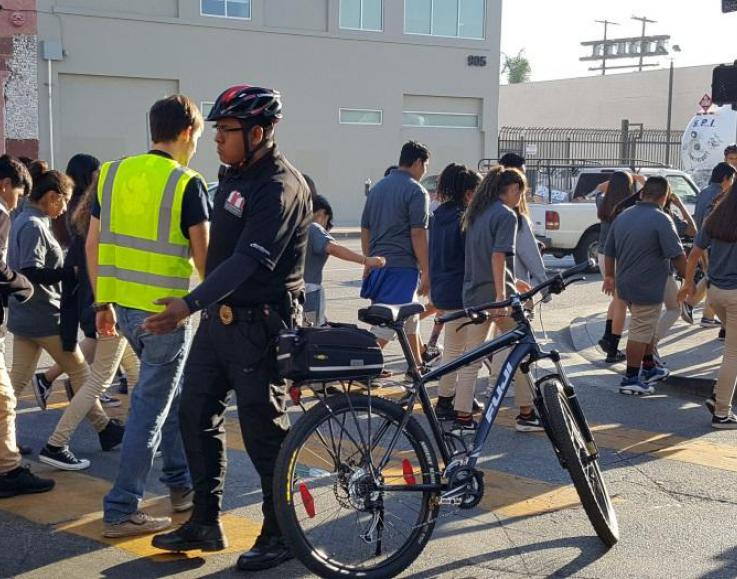 IDBID Bike Safety Officer at intersection as students walk to arts classes