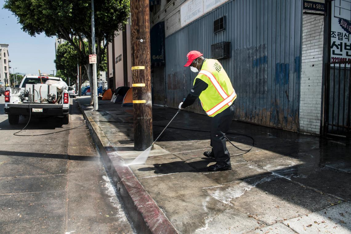 BID staff pressure washing to clean the sidewalk.